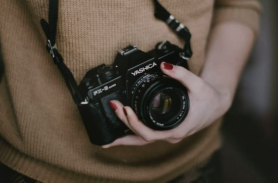 Girl In Brown Sweater Holding Camera - Should you copy other photographers?